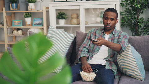 Bored African American guy is watching boring film on TV eating popcorn and Footage