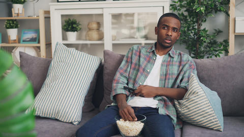 Emotional African American man is watching thriller on TV at home and eating Live Action