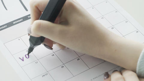 Woman's hand writing with Violet felt pen on calendar word vacation Footage