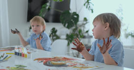 little child with hands painted in colorful paints ready for hand prints Footage