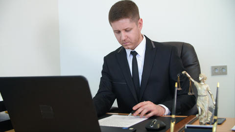 Professional lawyer reading and signing document on work table in law office Live Action