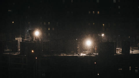 Construction site workers construct at winter night in bad weather conditions Footage