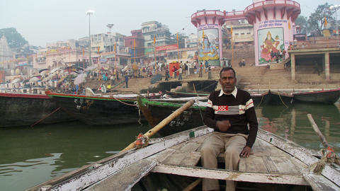 Man talking and rowing boat toward Indian city docks Footage