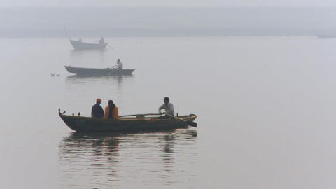 A few boats being rowed on foggy water Footage