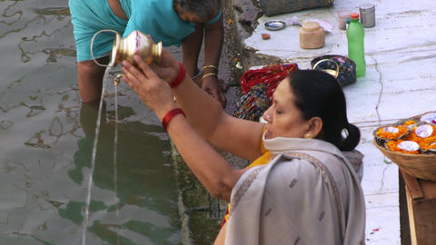 Close up view of woman pouring holy water into ganges river Footage