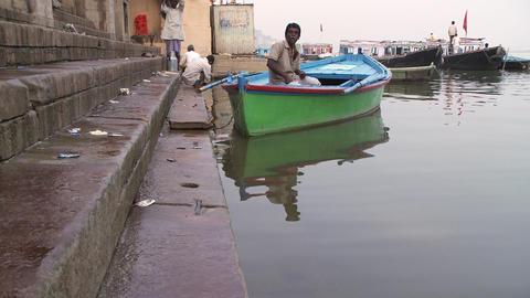 Man in a colorful boat waits by the wharf. Shot from a low angle Footage