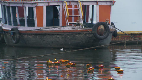 A dozen floating flower candles in water float past large wooden boat Live Action