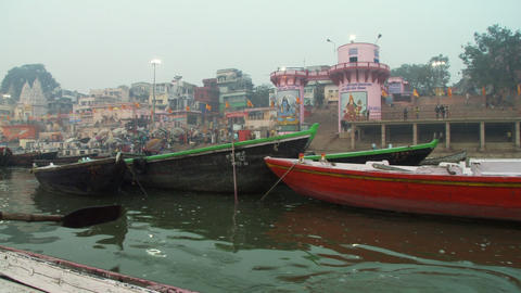 Shot passing several moored boats on the Ganges river. City in the background Footage