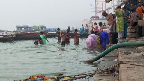 Small crowd of people bathing in the Ganges river Footage