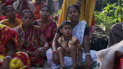 Several Indian women sitting on the ground reciting together Live Action
