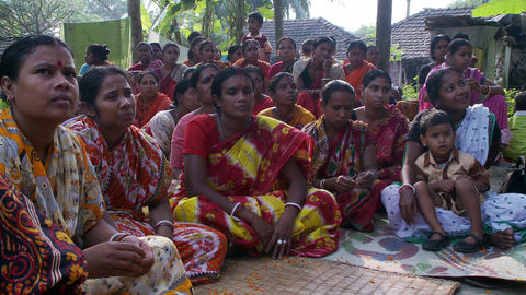 Crowd of Indian women sitting on the ground, listening to an unseen speaker Live Action