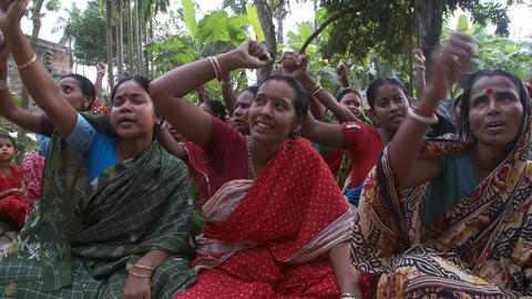 Small crowd of Indian women sitting on the ground, chanting and waving arms Live Action