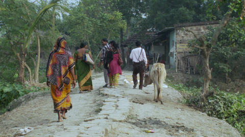 Villagers in India walking down dirt path Footage