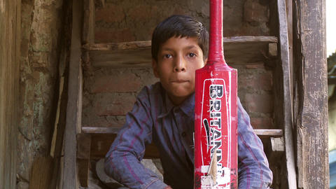 Boy looking, nodding holding red cricket bat Footage