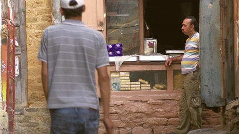 Man in stripes waiting at a counter man wearing jeans and white hat walks past s Footage