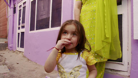 little girl chewing on wrapper wearing yellow sleeved shirt lady in yellow stand Live Action