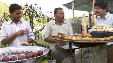 Fried food vendors cutting bread, man cooking dough and man watching vendors coo Footage