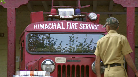 Indian man inspecting fire truck Live Action
