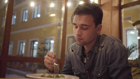 Portrait of a young thoughtful guy eating at a restaurant alone. A sad man is Footage