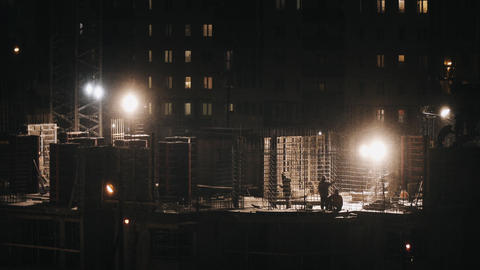 Construction site residential welding workers construct at winter night snowing Footage
