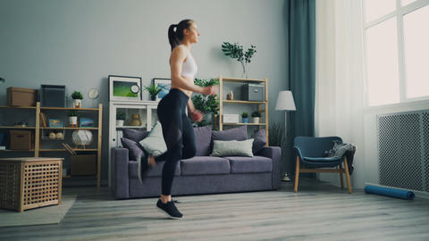 Good-looking girl student doing exercises at home running on the spot in flat Footage