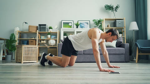Sportsman touching smartphone screen then practising plank position at home Footage