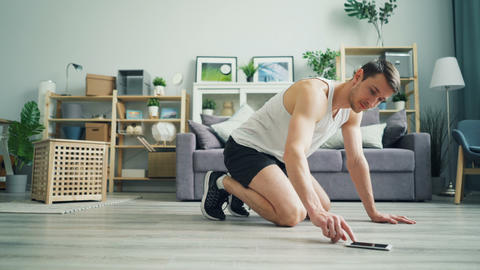 Handsome man exercising at home doing cardio exercise in plank using smartphone Footage