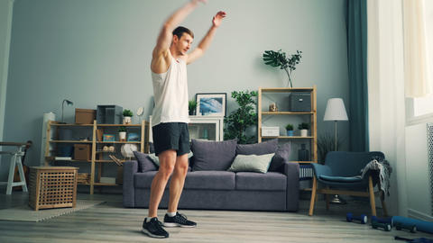 Active sportsman exercising at home rotating arms doing exercises for shoulders Live Action