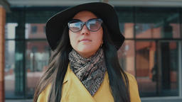 stylish girl in a hat and glasses walking down the street Footage