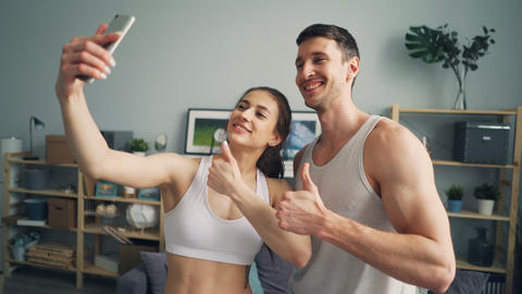 Sporty young couple taking selfie together posing for smart phone camera at home Footage