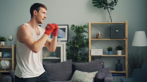 Muscular guy in sportswear boxing alone indoors in apartment enjoying activity Footage