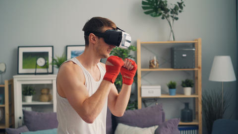 Young male boxer training indoors alone at home wearing virtual reality glasses Footage