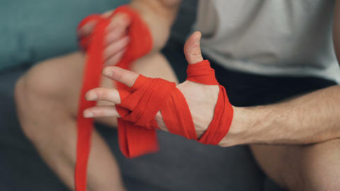 Closeup shot of man wrapping hands with protective wrist bandages clapping hands Footage