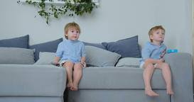 The kids are watching tv. Small children sitting on the couch watching cartoons Footage