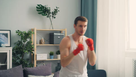 Handsome sportsman with wrapped wrists boxing indoors at home exercising alone Footage