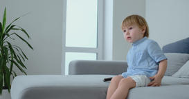 A 2 years old boy sits on a sofa and watches TV while sitting with the remote Footage