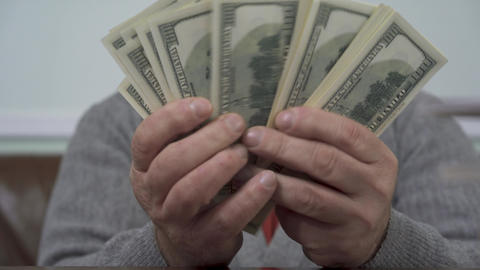 Hands of the old man counting dollars close up. Positive rich man demonstrates Live Action