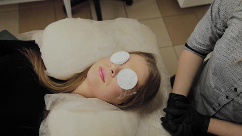 A very beautiful girl in a beauty salon does a lamination lashes. Waiting for Footage