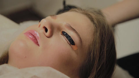 A very beautiful girl in a beauty salon does a lamination lashes. Lying awaiting Live Action