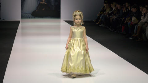 Moscow, Russia - March 21, 2019: little girl defiles in golden dress with Footage