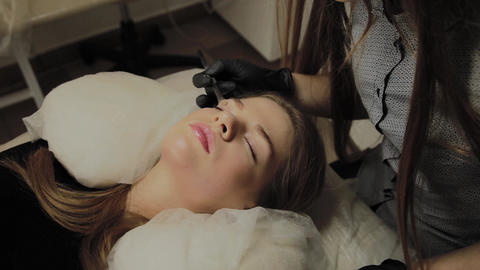 A very beautiful girl in a beauty salon does a lamination lashes. Beautician Live Action