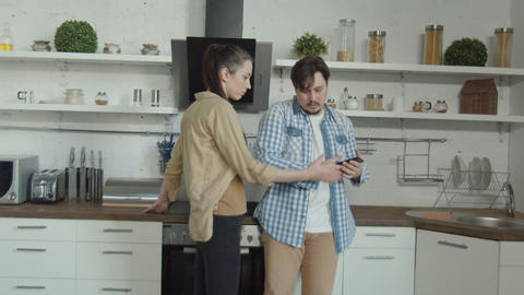 Woman finding out man cheating by phone in kitchen Live Action