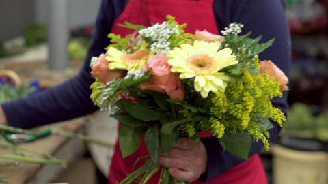 Close up of female florist creating beautiful bouquet at flower shop Footage