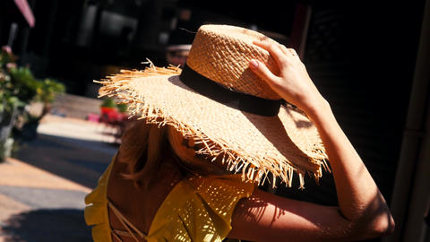 A cute young woman in a straw hat smiles and whirls holding a straw hat Live Action