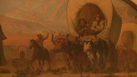 Tight shot of a painting depicting pioneers crossing the western United States Footage