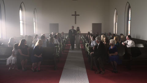 People turning to watch a father escort a bride down the aisle Footage