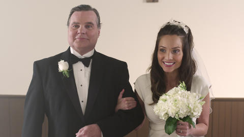 Shot in front of a father and bride walking down the aisle smiling Footage