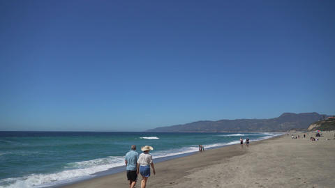 Retired Couple Walks Along The Beach At Point Dume stock footage