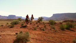 Shot of man and woman on horseback while travelling in the Moab Desert with lens Footage