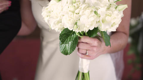 Shot of a bride's wedding ring and bouquet as she walks down the aisle Footage